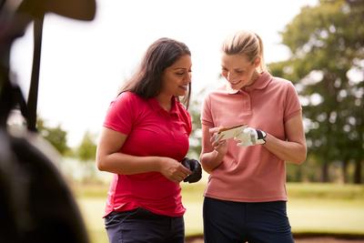 Two golfers marking scorecard