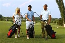 Happy partners standing on golf course, choosing golf club from